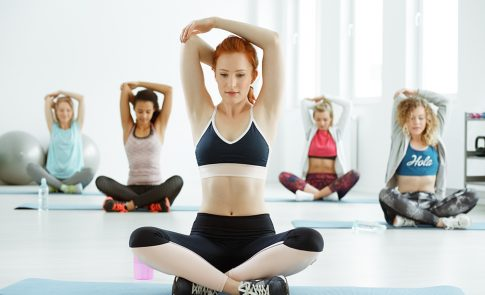 Young active women doing arm stretching on fitness classes